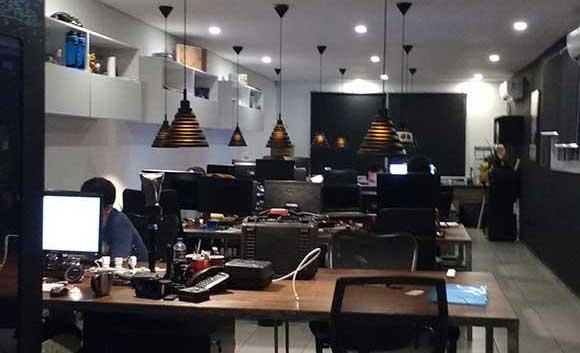 Sala moderna com pessoas trabalhando com IoT, wearables, realidade virtual, instalações digitais e impressão 3D